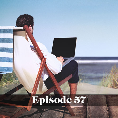 Man working while using a laptop at the beach