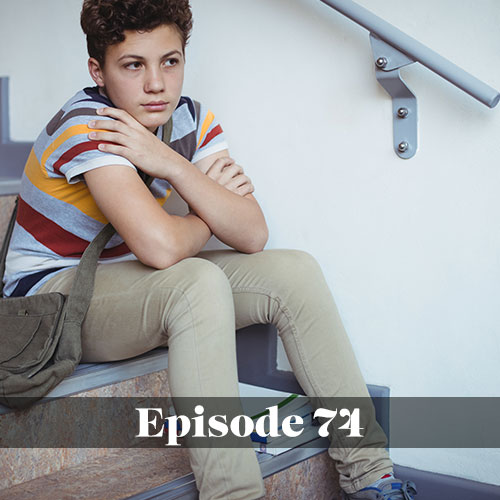 Sad boy sitting on steps at school in post about mental health in the school setting