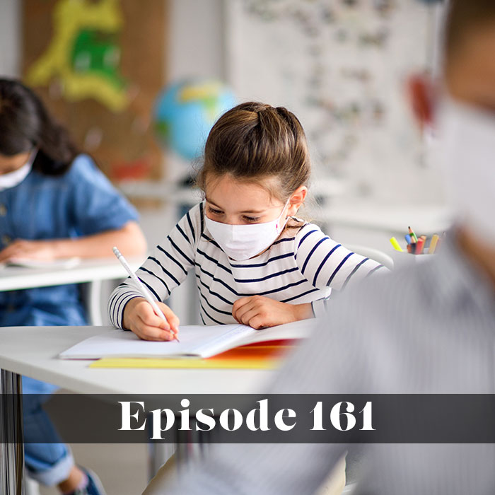 Opening schools during a pandemic, young child wearing a mask in a socially distant fully opened school